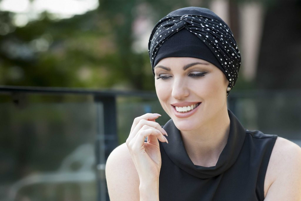 A woman wearing a black hat with a polka dot headband called Chemo Hat - Ella Black and White Polka Dot